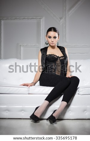 Sexy brunette in black clothes posing on white sofa - stock photo