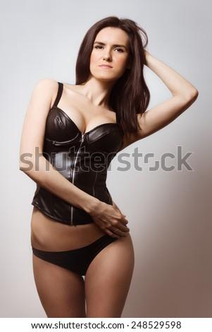 Sexy brunette in black latex corset - stock photo