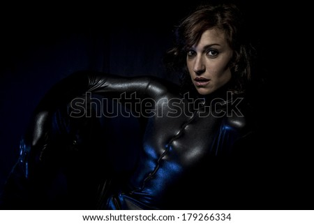 Sexy brunette in black latex costume, Fashion shot of a woman in black glossy