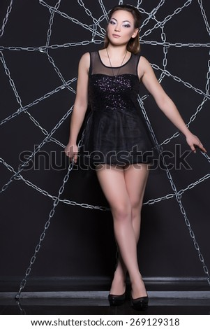 Sexy brunette in black short dress posing at the web of chains - stock photo