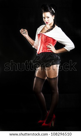 sexy brunette in red corset, red heels, black stockings and black miniskirt - stock photo