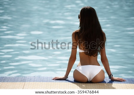 Sexy brunette in the white bikini on the sun-tanned slim and shapely body is resting and taking sun bathes near the swimming pool - stock photo