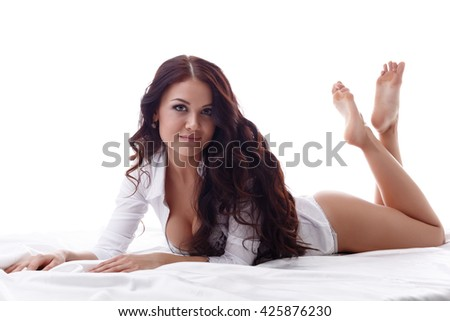Sexy brunette looking at camera while lying in bed