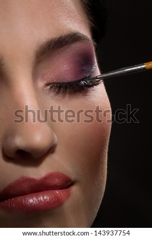 Sexy brunette putting mascara makeup in darkness - stock photo