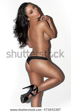 Sexy brunette topless woman wearing black panties and high heels posing and looking into the camera over white background