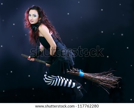 Sexy brunette witch flying on broom on a dark sky with stars - stock photo