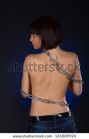Sexy brunette with nude back in chains over black background - stock photo