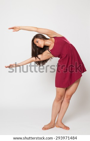 Sexy brunette woman dancing in red dress. - stock photo