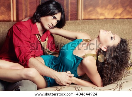 Sexy brunette woman in a blue dress and attractive hot man enjoying on a sofa in a luxury room. - stock photo