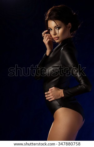 Sexy brunette woman in leather black clothes over dark background