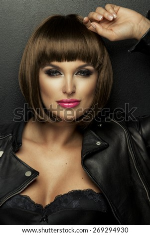 Sexy brunette woman in leather jacket - stock photo