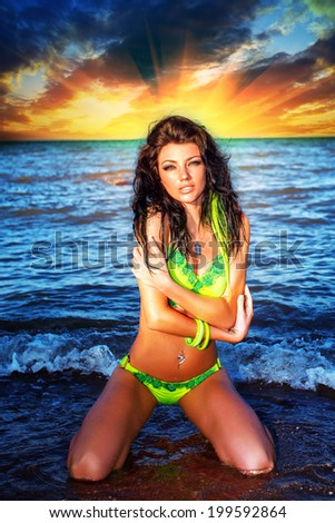 sexy brunette woman in water at sunset  - stock photo