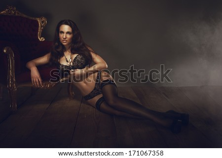 Sexy brunette woman lying on wooden floor - stock photo