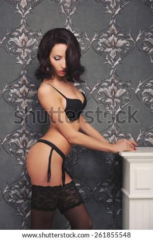 Sexy brunette woman near fireplace posing on vintage wall, seduction - stock photo