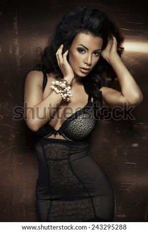 Sexy brunette woman posing in elegant lingerie, looking at camera.  - stock photo
