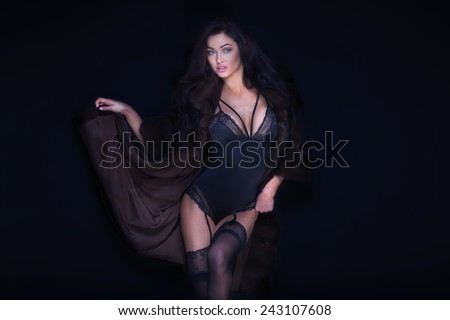 Sexy brunette woman posing in elegant lingerie, looking at camera. Girl with perfect body. Studio shot. - stock photo