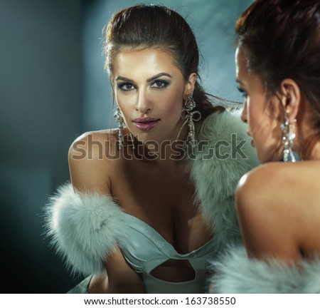 Sexy brunette woman posing wearing white fur and elegant jewelry. - stock photo