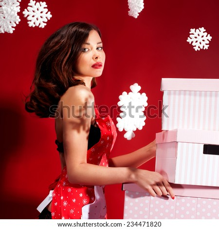 Sexy brunette woman preparing christmas gift. Girl wearing lingerie and kitchen apron.