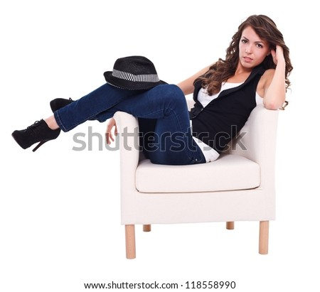 Sexy brunette woman sitting in armchair, posing to camera - stock photo