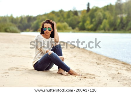 Sexy brunette woman sitting on a beach