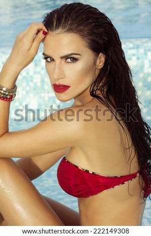Sexy brunette woman sunbathing near swimming pool. Girl looking at camera. - stock photo