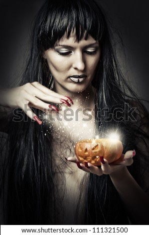 Sexy brunette woman witch making magic to pumpkin - stock photo