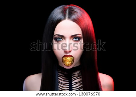 Sexy brunette woman with a spiky toy on a black background - stock photo