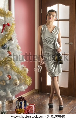 sexy brunette woman with elegant silver dress and heels in christmas indoor shoot near decorated tree and with bottle of champagne and glass in the hand. xmas or new year night party  - stock photo