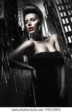 sexy brunette woman with red lips in dark rainy city - stock photo