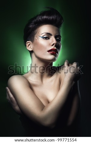 sexy brunette woman with red lips in green light - stock photo