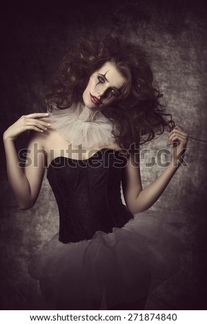sexy brunette woman with sad clown masquerade, wearing romantic tutu and bizarre hair-style. Romantic vintage carnival portrait  - stock photo