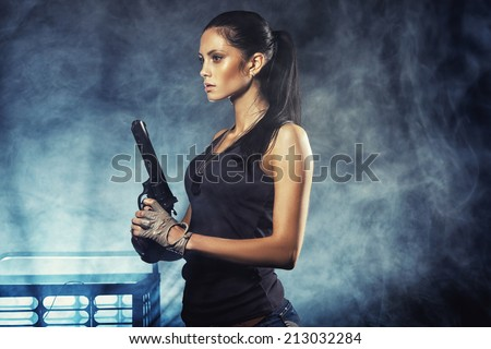 sexy brutal woman standing on factory ruins and holding handgun - stock photo