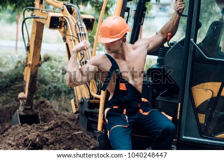 Sexy builder concept. Muscular builder in hard hat shows biceps, poses. Sexy man with nude torso near construction equipment or excavator on background. Handsome man or bodybuilder wears overalls.