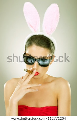 sexy bunny woman wearing sunglasses smoking on a big cigar - vintage picture style - stock photo