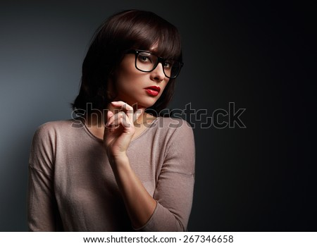 Sexy business thinking woman looking in fashion eyes glasses on black background - stock photo