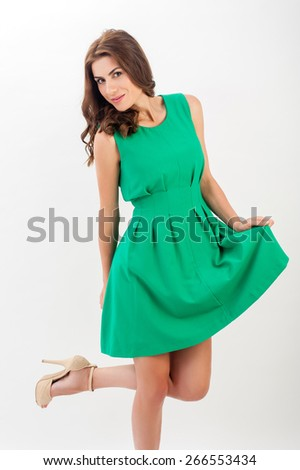Sexy business woman excited. Beautiful happy caucasian model standing playful in green dress isolated on white background. - stock photo