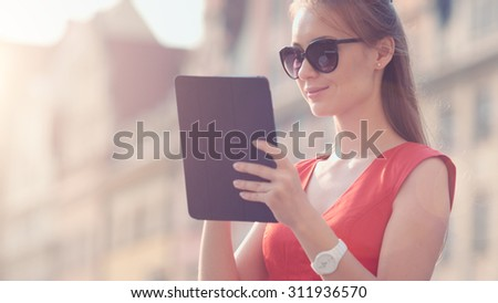 Sexy Business Woman using digital tablet. Slow Motion. Beautiful woman in red high-heeled shoes and dress enjoying sunny morning in the city, browsing Internet. Lens Flare. - stock photo