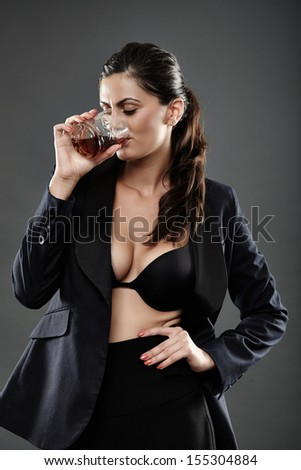 Sexy businesswoman in bra and suit drinking a glass of brandy