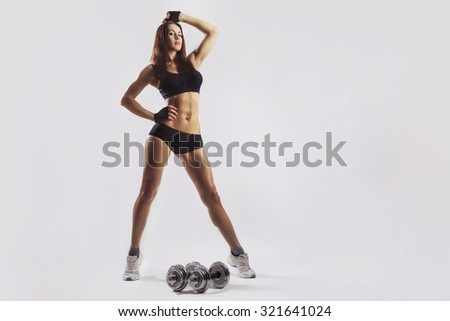 sexy busty young woman in a bikini workout training with dumbbells isolated studio portrait