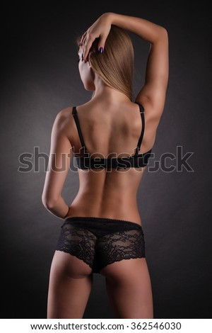 Sexy buttocks in black lingerie over dark background