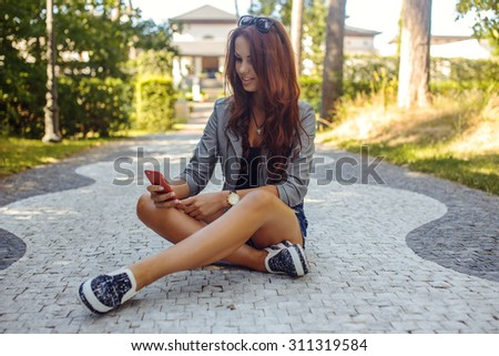 Sexy casual female sitting on the road in park and chatting with smartphone. - stock photo