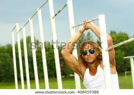 sexy caucasian fit man in sunglasses posing near Sports Bars Outdoors. muscular man posing outdoor - stock photo