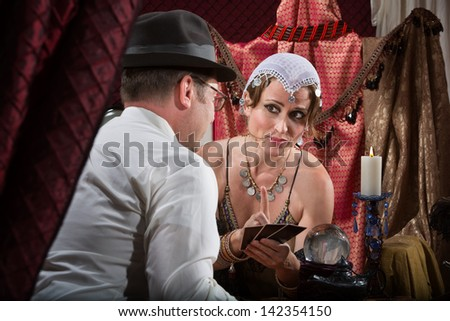 Sexy Caucasian tarot card reader with male customer - stock photo