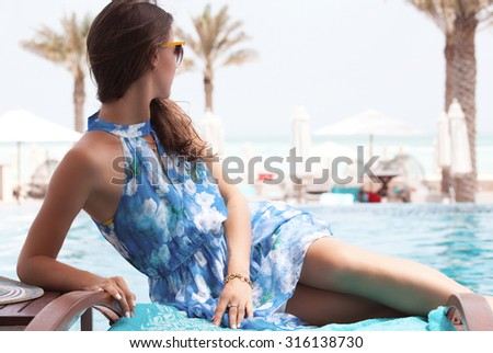 Sexy cheerful woman in dress relaxing at the luxury pool. Girl at travel spa resort. Summer luxury vacation. - stock photo