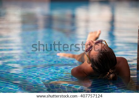 Sexy cheerful woman relaxing at the luxury poolside. Girl at travel spa resort pool. Summer luxury vacation. (focus on head)