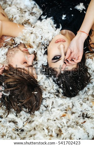 sexy christmas couple of pretty sexy woman or cute girl with long hair and fashionable makeup, handsome man with bare chest lying on white feathers as decorative new year snowflakes