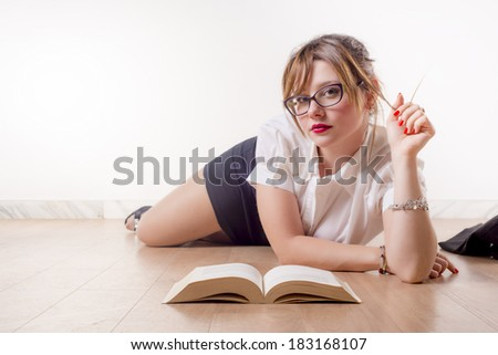 Sexy college girl reading a book on the floor