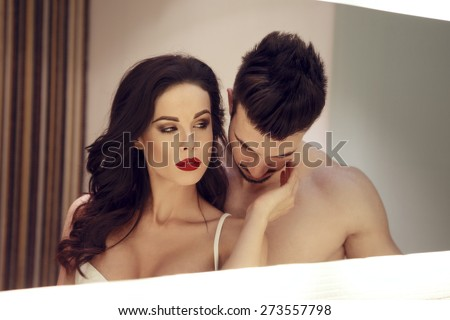 Sexy confident milf woman with young lover posing in mirror - stock photo