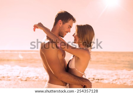 Sexy couple embracing on the beach - stock photo