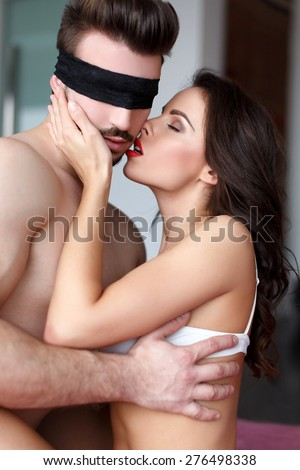 Sexy couple foreplay at home, milf with young lover, macho man with lace eye cover - stock photo